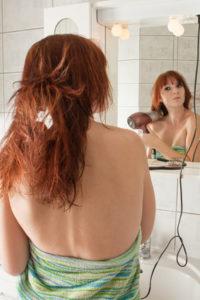Hübsche Frau bürstet und fönt sich die Haare